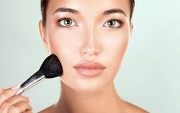 Pretty woman holds makeup brush stock images