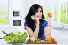 Pretty woman holds a slice of tomato Stock Photography
