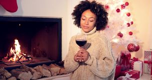 Pretty woman holds wine glass beside fireplace stock video footage