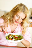 Pretty woman at home eating salad of vegetables Stock Photo