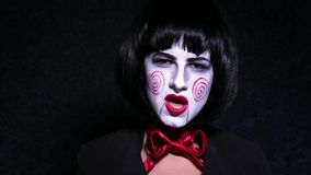 Pretty woman in horror style make up sings a song on dark background Stock Photos