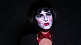 Pretty woman in horror style make up sings a song on dark background Stock Image