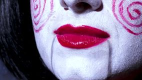Pretty woman in horror style make up sings a song on dark background Royalty Free Stock Images