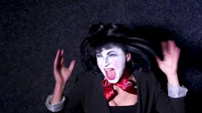 Pretty woman in horror style make up sings a song on dark background Royalty Free Stock Image