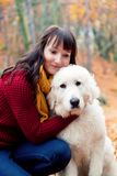Pretty woman hugging cute puppy dog in autumn park Royalty Free Stock Images