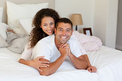 Pretty woman hugging her husband on their bed Royalty Free Stock Photos