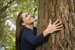 Pretty woman hugging a tree Stock Images