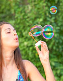 Pretty woman inflating soap bubbles Royalty Free Stock Photography