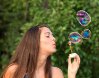 Pretty woman inflating soap bubbles Stock Photography