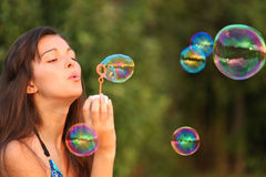 Pretty woman inflating soap bubbles Stock Image