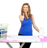 Pretty woman ironing with thumb up Stock Photo