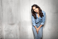 Pretty woman in jeans watchig at camera. Curly brunette pretty woman in jeans watchig at camera om gray cement background Royalty Free Stock Images