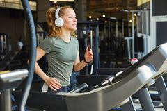 Pretty woman jogging in gym stock photos