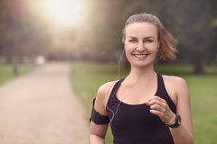 Pretty Woman Jogging at the Park with Headphones Royalty Free Stock Photography
