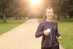 Pretty Woman Jogging at the Park with Headphones Stock Image