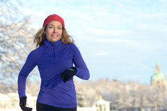 Pretty Woman Jogging in winter with earphones Royalty Free Stock Image