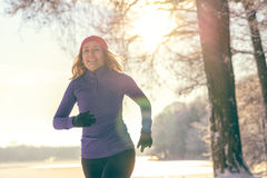 Pretty Woman Jogging in winter with earphones Stock Image