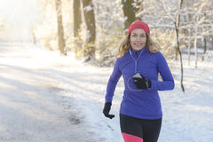 Pretty Woman Jogging in winter with earphones Royalty Free Stock Photography