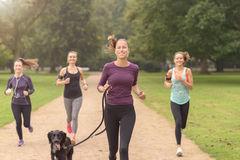 Pretty Woman Jogs in the Park with Other Girls Stock Photography