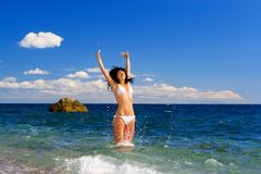 Pretty woman jump on the sea Stock Photography