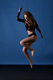 Pretty woman is jumping in studio wearing sequins jacket, shorts Royalty Free Stock Images