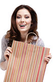 Pretty woman keeps paper gift bag. Isolated on white Royalty Free Stock Photography