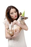 Pretty woman kisses a straw-colored small dog. In cap, isolated on white Stock Image