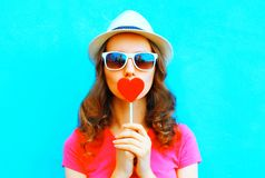 Pretty woman kissing red lollipop shape of a heart. Over colorful background stock images