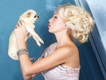 Pretty woman kissing small dog Stock Images