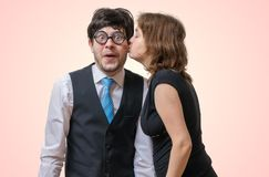 Pretty woman is kissing surprised nerd Stock Photography