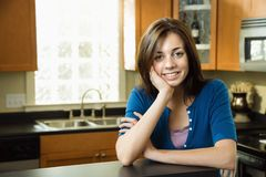Pretty woman in kitchen stock photography