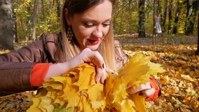 Pretty woman knits yellow maple leaf wreath. And smiles in forest on background of trees with yellow foliage in autumn. Woman in orange sweater and brown stock footage