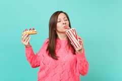 Pretty woman in knitted pink sweater with closed eyes hold in hands eclair cake, plastic cup of cola or soda isolated on. Pretty woman in knitted pink sweater royalty free stock images