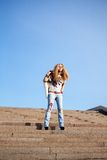Pretty woman on a ladder against the blue sky. Stock Images