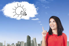 Pretty woman with lamp on the cloud Stock Image