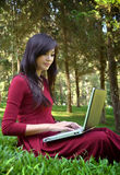Pretty  woman with laptop. On green grass at the garden Royalty Free Stock Photos