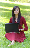 Pretty  woman with laptop. On green grass at the garden Stock Photography