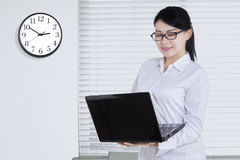 Pretty woman with laptop and clock Royalty Free Stock Photography