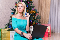 Pretty woman with laptop credit card buying presents Christmas t Royalty Free Stock Image