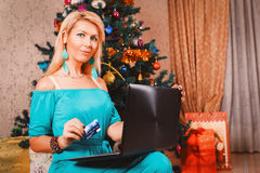 Pretty woman with laptop and credit card buying presents near Ch. Ristmas tree Royalty Free Stock Photos