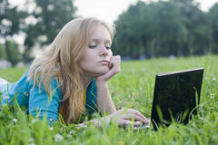 Pretty woman with laptop on the green grass Royalty Free Stock Images