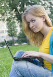 Pretty woman with laptop on the green grass Stock Images