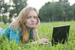 Pretty woman with laptop on the green grass Stock Photos