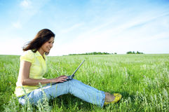 Pretty woman with laptop on the green grass Royalty Free Stock Image