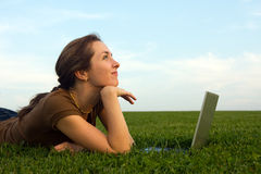 Pretty woman with laptop on the green grass Stock Image
