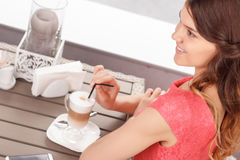Pretty woman with latte in cafeteria Royalty Free Stock Photography