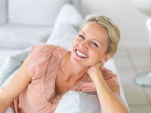 Pretty woman laughing while sitting on the couch Stock Photography