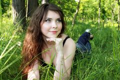 Pretty woman lay in green grass Royalty Free Stock Images