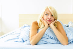Pretty woman laying in bed daydreaming stock photos