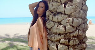 Pretty Woman Leaning Against Beach Palm Tree Trunk stock footage